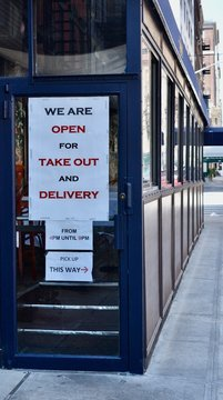 Sign in the window of a restaurant We Are Open For Take Out And Delivery with business hours, March 27, 2020, in New York.