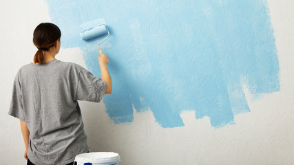 Woman paint wall at home, free space