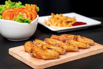 fast food , french fries and fried chicken , with green salad, tomatoes on dark table