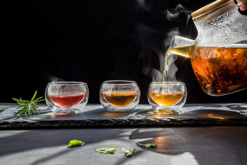 Photo Blinds Tea Cup of hot tea cane sugar dry tea leaves ,Hot tea in glass cup with steam and lemon .hot food and healthy meal concept