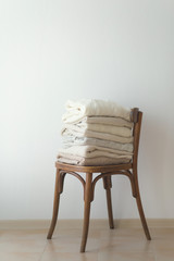 Stock Photo - Stack of cozy knitted sweaters on a wooden chair