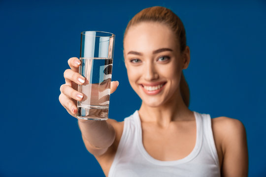 Girl Offering Glass Of Water To Camera Over Blue Background
