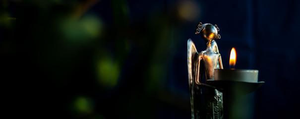 Fototapeta Metallic angel holding a flame of hope obraz