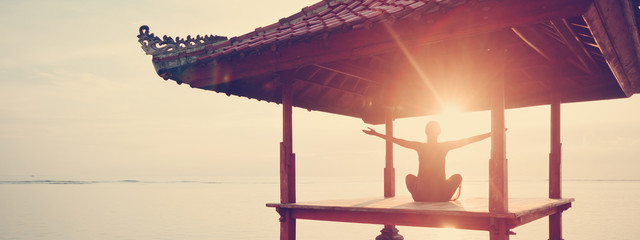 Fotomurais - Woman greetings sun, doing fitness practice near ocean. Wide screen panoramic