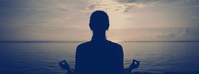 Fotomurais - Silhouette of young woman doing yoga on the beach. Wide screen panoramic