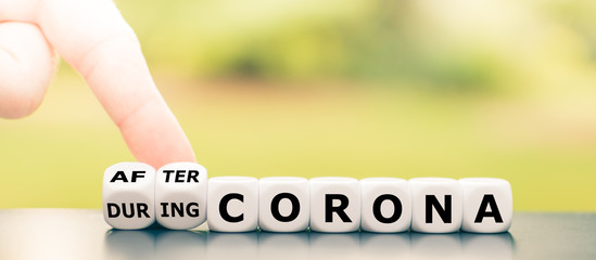 "Hand turns dice and changes the expression ""during Corona"" to ""after Corona""."