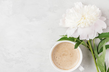 Morning cup of coffee with white peony flower on light concrete background. flat lay. top view