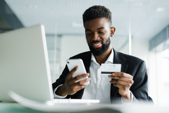 African American man paying with credit card online while making orders via mobile Internet making transaction using mobile bank application.