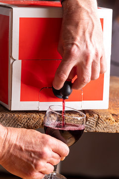 pouring red wine from a box