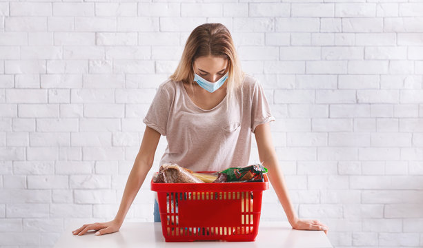 Woman in mask bent over basket of products