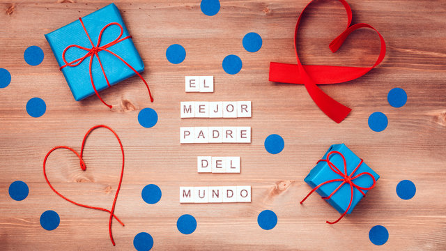 El mejor papa del mundo words that mean best dad in the world made of wooden blocks with blue gift boxes and red hearts on wooden background. Happy fathers day greeting card, top view