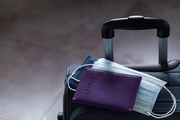Travel suitcase, passport and medical mask. The ban on travel during the epidemic of the...