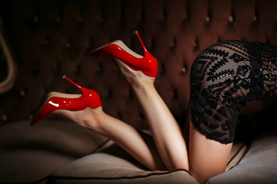 Beautiful woman's body. Slim girl with lovely round ass and long legs with high heels posing on a dark brown sofa.