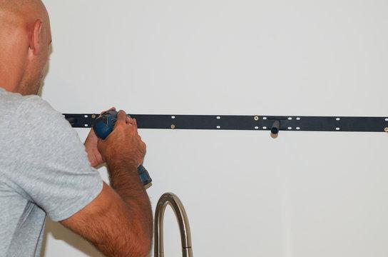 Man's hands screwing a shelf holder with a screw gun on a wall - close-up