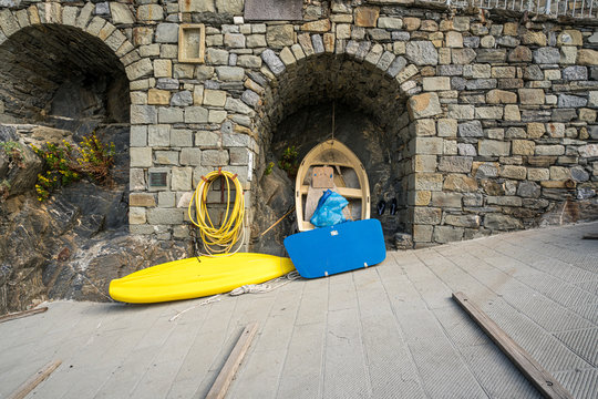 Medieval brick wall and yellow surfboard in  in Manarola town, Italy
