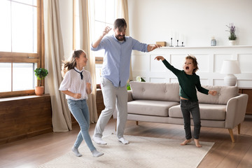 Excited young father enjoying funny family activity with small kids in living room. Energetic...