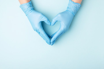 Fototapeta Doctor's hands in medical gloves in shape of heart on blue background with copy space. obraz