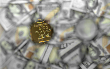 A part of a 500 gram gold bar against the background of a fragments of hundred-dollar bills. Selective focus.