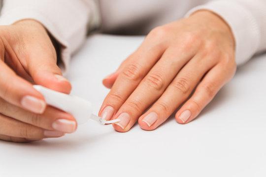 close up woman varnishing nails at home. self nail strengthening while in quarantine