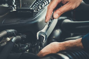 Professional mechanic providing car repair and maintenance service in auto garage. Car service business concept.