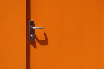 Bright orange metal door with handle close-up. Modern exterior Wall mural