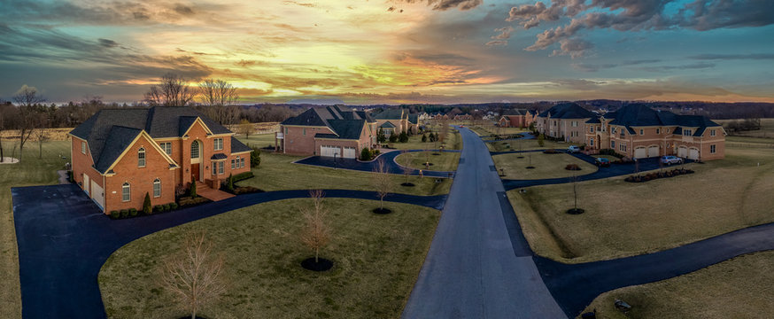 Sunset aerial view of American luxury estate homes with long driveways in Maryland USA