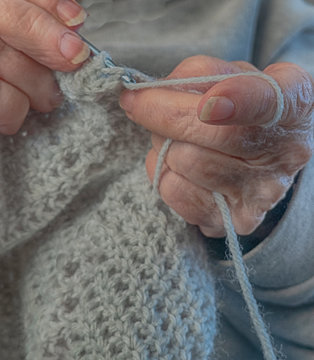 Hands doing the age old art or craft with thread called crochetting.