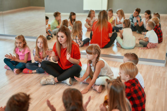 Having some fun after choreography class. Young female dance teacher with group of happy children clapping and playing while sitting on the floor in dance studio