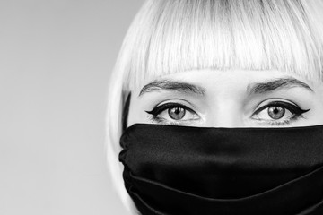 Woman wearing protective handmade black face mask looks at camera. Monochrome close up portrait. Copy, empty space for text Fotoväggar