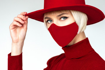 Woman wearing trendy fashion outfit during quarantine  of coronavirus outbreak. Total red look including protective stylish handmade face mask Wall mural