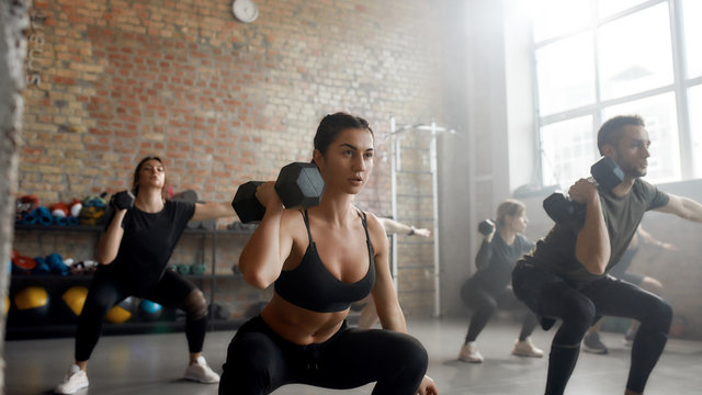 Play strong. Young athletic woman lifting dumbbell while having workout at industrial gym. Group training concept