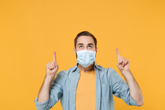 Young man in sterile face mask posing isolated on yellow background studio portrait. Epidemic pandemic rapidly spreading coronavirus 2019-ncov sars covid-19 flu virus concept. Point index fingers up.
