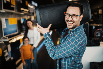 Photo sur Toile Magasin de musique Happy family buying large music speaker in tech store.