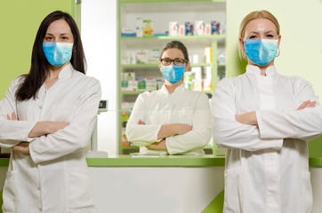Three serious female pharmacists with protective clothes, doing their job in pandemics