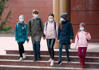 Children students in medical masks leave the school.
