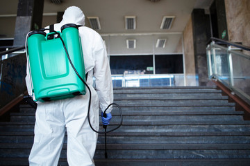 Shot of an unrecognizable person in white chemical protection suit with reservoir disinfecting public corridor to stop spreading highly contagious corona virus. Fight against coronavirus or COVID-19.