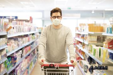 Coronavirus, Mann schützt sich im Laden mit Atemmaske und Handschuhen vor einer Ansteckung