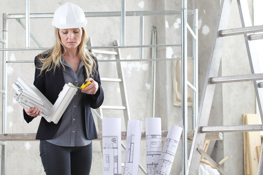 woman architect or construction interior designer with with meter measuring white windows cutaway profile inside a building site with ladder and scaffolding in the background