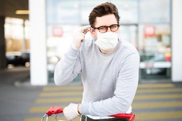 Mann vor einem Supermarkt zieht eine Atemschutz-Maske an um sich vor dem Corona-Virus zu schützen Fototapete