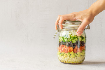 Vegetables salad in a jar isolated on grey background. Hand is holding a jar. Close up. Copy space. Healthy food, vegetarian dish, lunch or dinner. Homemade recipe. Take away concept. Fototapete
