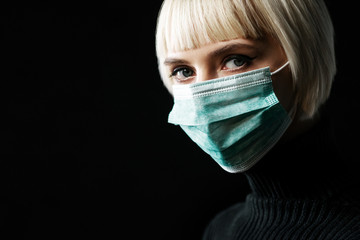 Woman wearing medical protective face mask looks at camera, posing on black background. Copy, empty space for text Wall mural