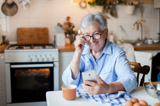 Senior woman using mobile phone at home kitchen. Happy retired person shopping online. People connection, virtual communication, distance healthcare. Pensioner in social distancing, isolation.