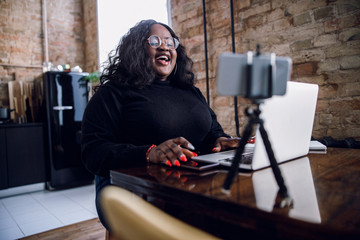Laughing blogger at home with gadgets stock photo