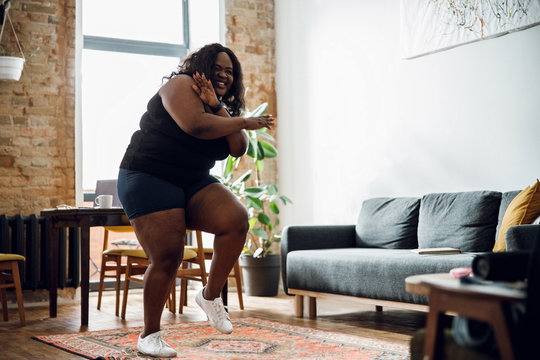 Positive plus size woman dancing at home stock photo