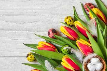 Easter background with Easter eggs and spring tulip flowers on white wooden background. flat lay. top view