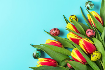 Easter background with Easter eggs and spring tulip flowers on pastel blue background. flat lay. top view