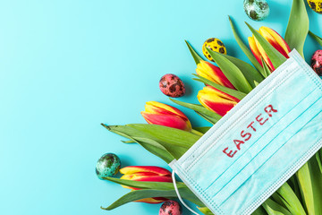Easter time in coronavirus covid 19 quarantine concept. Face medical mask on tulip flowers with eggs on blue background