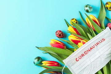 Coronavirus quarantine during Easter holidays. spring tulip flowers with face medical mask and eggs on blue background