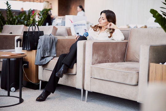 Beautiful young woman reading book in departure lounge