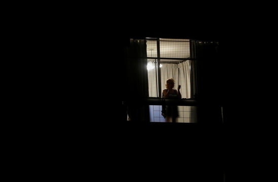 A woman joins a citywide applause as people clap from their balconies and windows to show appreciation and support for the health workers as the spread of the coronavirus disease (COVID-19) continues, in Buenos Aires